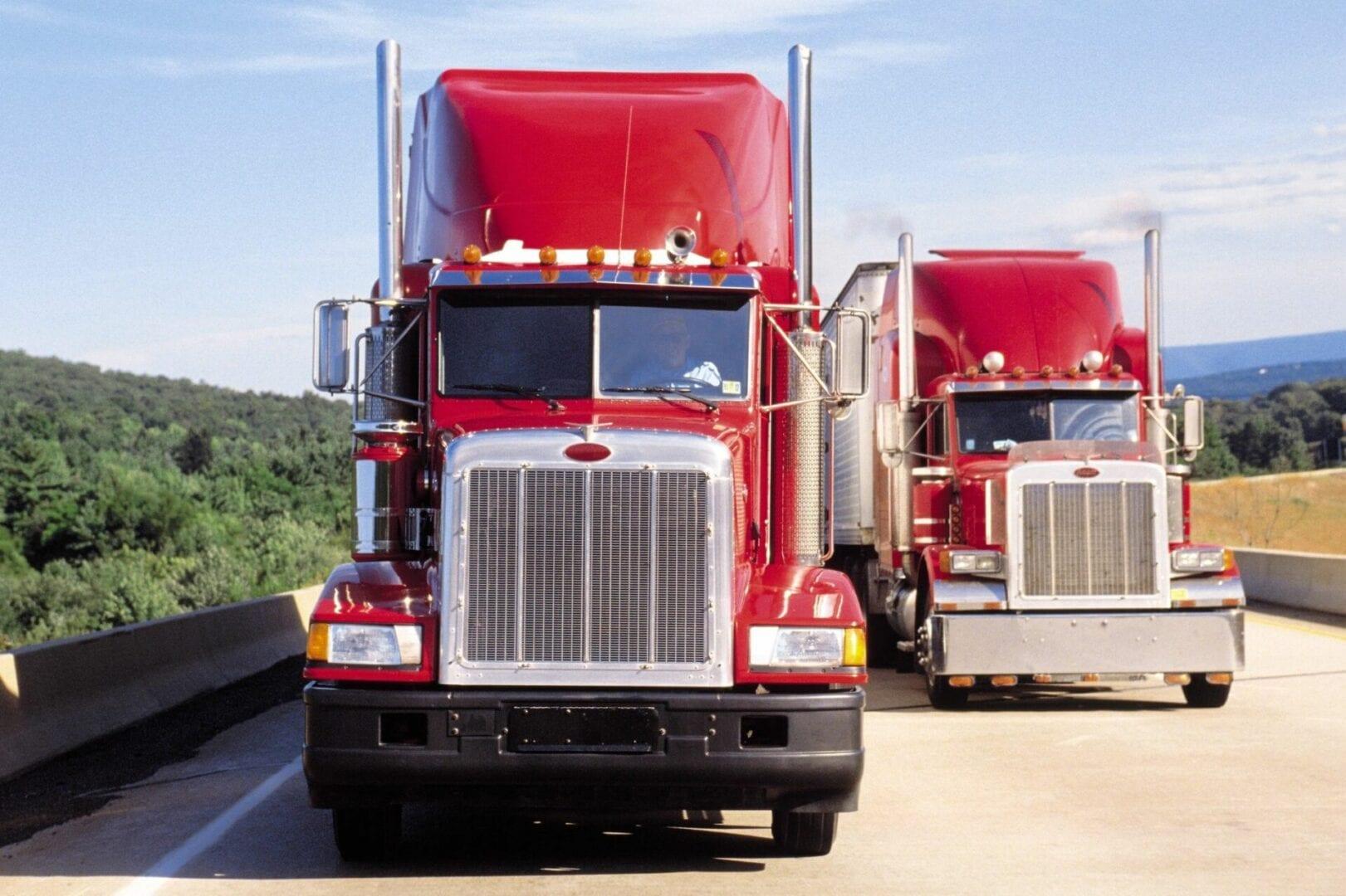 2 red peterbilt trucks