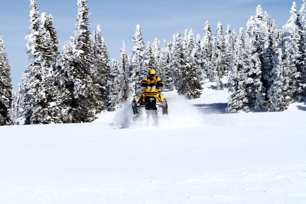 Snowmoblier coming out of the trees in deep powder snow using AMSOIL