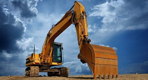 Excavator with it's scoop touching the ground.