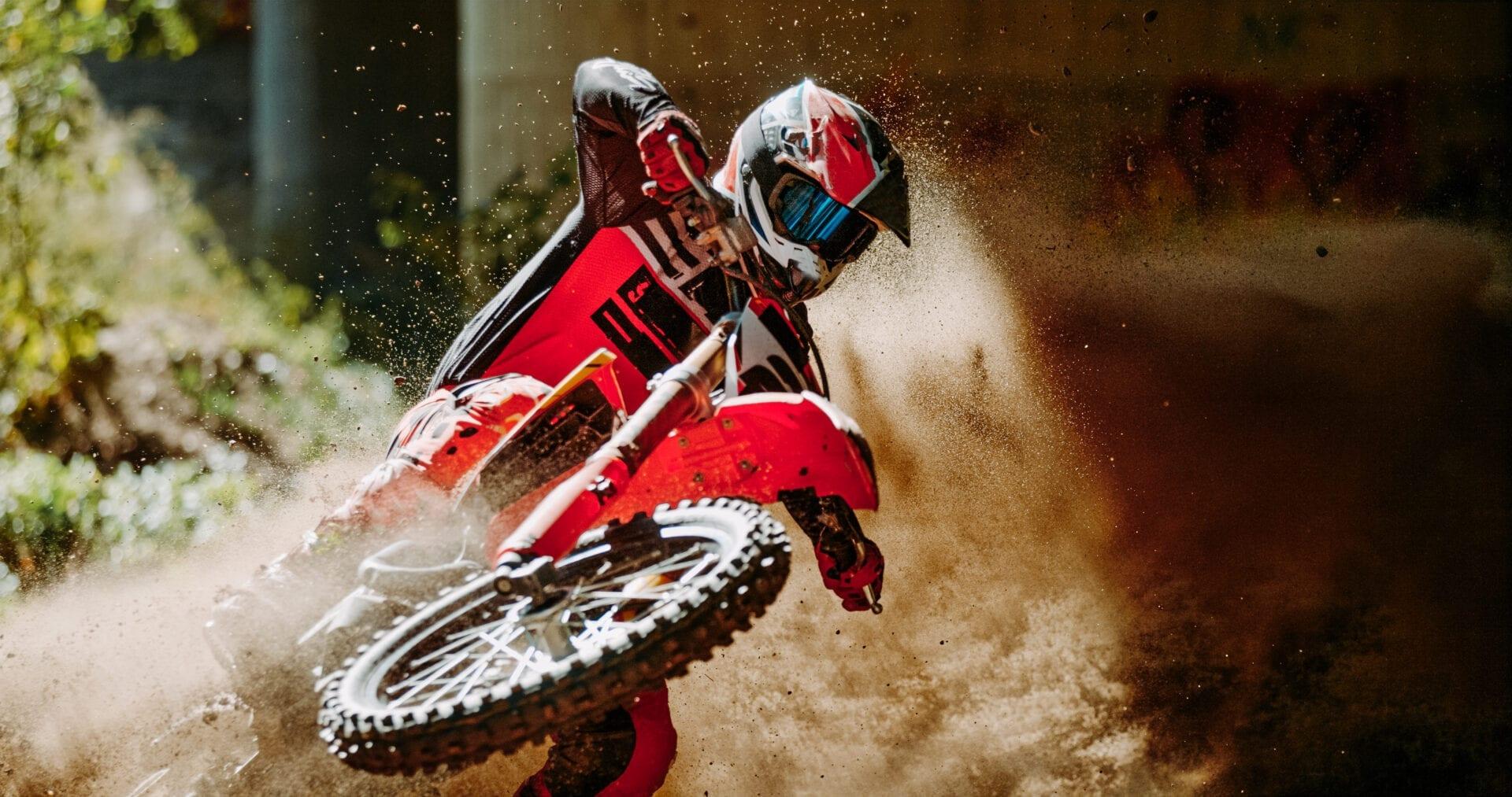 Dirt biker making a turn on a dirt track.