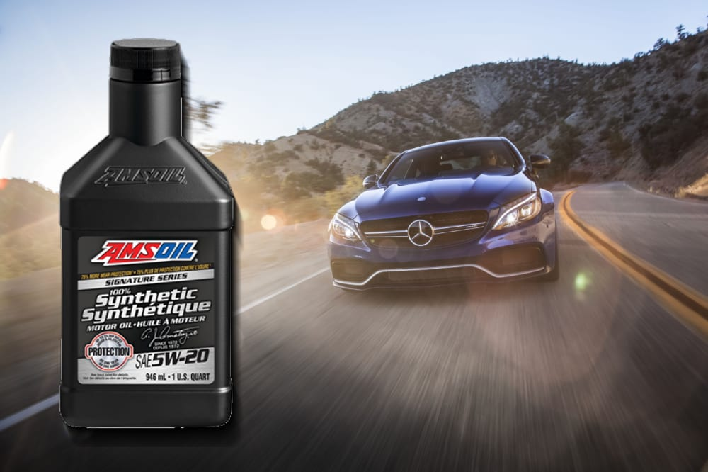 AMSOIL 5W-20 Synthetic motor oil in front of a Mercedes-Benz driving on a road